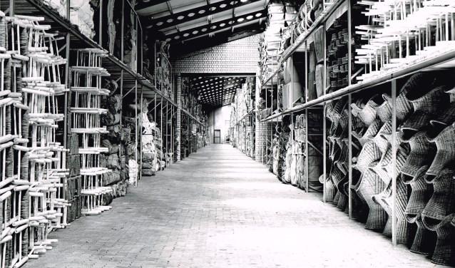 Heemkundekring Onsenoort heeft een expositie samengesteld over de mandenmakerij in Vlijmen. Op deze foto zie je de opslag van rietwerk bij Rietwerk Verboord, producten geïmporteerd vanuit Oost-Europese en Aziatische landen.