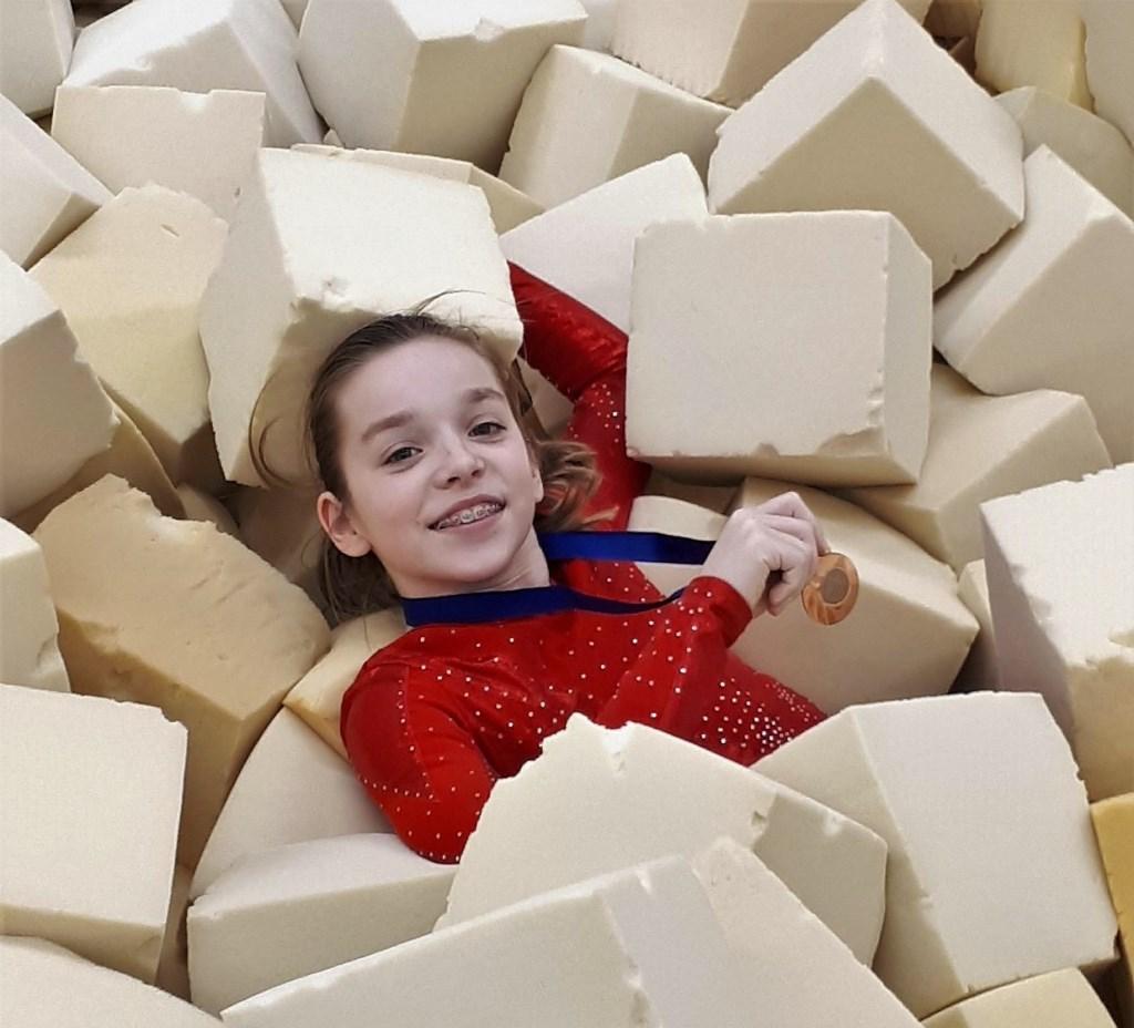Nienke de Heus belandt van louter vreugde met de medaille in de springkuil.  © Persgroep