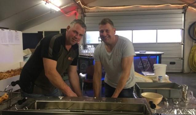 Willie van Vemde en Dennis Braakman aan het bakken. Ze hebben een speciale pan voor het bakken van de oliebollen aangeschaft.