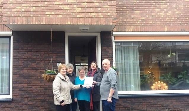 Uitreiking van het rapport van het onderzoek naar het wonen in de verbeterde woning aan de familie Meurs.Vlnr: Paula Voncken en Anita de Moed (beiden van de WAC), mevrouw Meurs (bewoner), Annelies Barnard (bestuurder de Woningstichting) en meneer Meurs (bewoner).