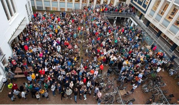 De foto toont het binnenplein van de school met leerlingen en medewerkers.