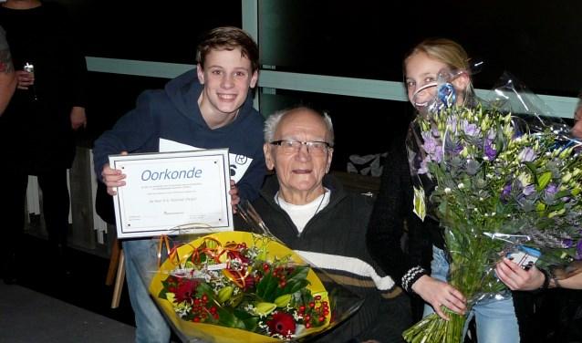 Geflankeerd door twee kleinkinderen zit VRB-oprichter Huug Paalvast verbaasd en trots te zijn over de eer die hem ten deel viel.