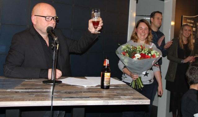 Robert Rinders tijdens zijn toespraak. Rechts met de bloemen jubilaris Liona van Maasakkers-Waanders.
