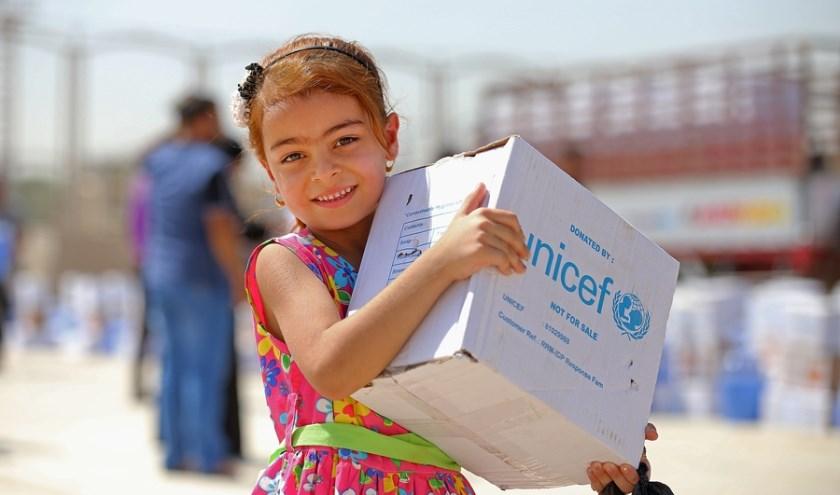 Kind in vluchtelingenkamp ontvangt hulpgoederen.