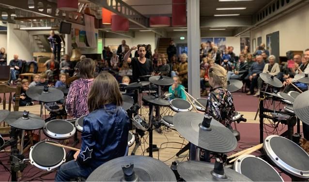 Leerlingen van de Muziekclub drummen erop los tijdens hun einduitvoering
