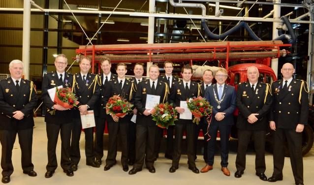 Tussen groep-chef Jan van Zee en burgemeester Harry Keereweer de gediplomeerden en jubilarissen. Rechts van de burgemeester Arnold van Doesburg en Erik van Zoelen.