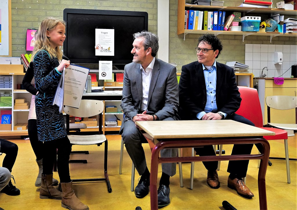 Dunya en Sterre overhandigen burgemeester Hans van der Pas en wethouder Peter de Rooij de brief over hondenpoep. (Foto: Max Timons)  © Persgroep