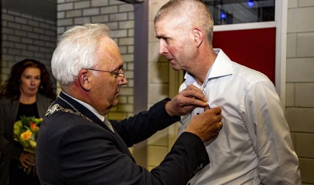Hildo de Lange krijgt zijn Koninklijke onderscheiding opgespeld door burgemeester Dirk van der Borg.