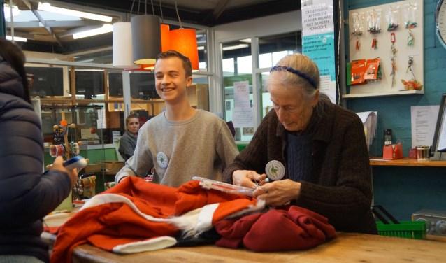 De jongste en oudste vrijwilliger werken samen als kassa-dienst. Over de toonbank gaan veel oude spullen die op weg gaan naar een nieuwe bestemming. Foto: Marielle Pelle