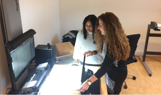 Angelique en Marcelina van het nieuwe scanteam zijn bezig om voor een klant een archiefstuk te scannen.