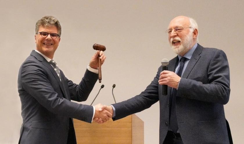 Commissaris van de Koning Hans Oosters (links) ontvangt de voorzittershamer uit handen van vicevoorzitter Kees de Kruijf.