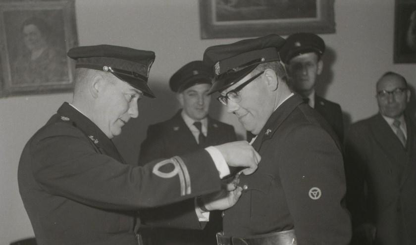 Op foto waa84084 ontvangt een brandweerman een onderscheiding. Wie weet wie de personen op deze foto zijn en wat er te vieren was?