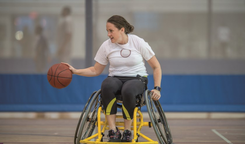 meisje in aangepaste rolstoel aan het basketballen