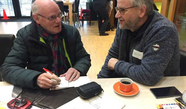 Energie-ambassadeur geeft bezoeker in het wijkcentrum advies.