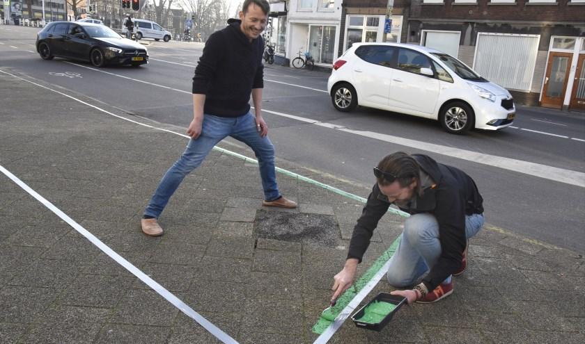 Marc Meijer en Olaf de Groot schilderen alvast de plantenvakken aan het Kleiwegplein. Foto: Marianka Peters