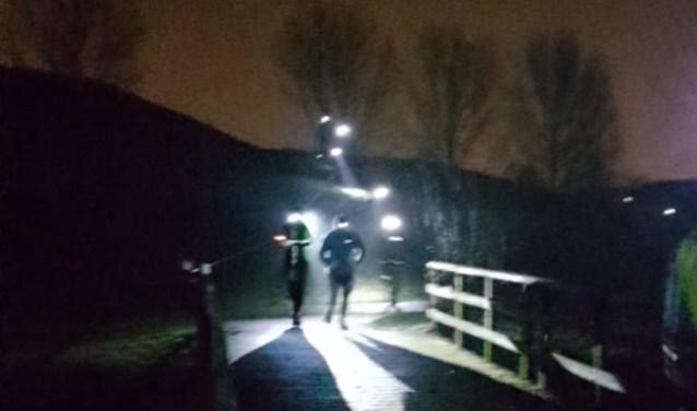 Trailrunners komen vanaf de heuvel richting verzorgingspost.