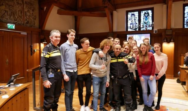 Politieagenten Rachid al Kahja en Eric Passchier gingen na afloop van de mediatraining voor de deelnemers aan het project 'Jeugd en Politiek' ook nog op de foto met een aantal leerlingen van de vijf Bredase scholen.