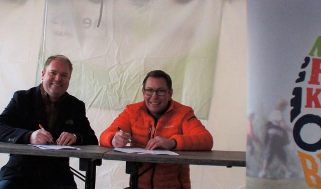 Hans van Kranenburg, voorzitter van de Stichtiing Nationale Rode Kruis Bloesemtocht, en Remco Boer, directeur Particulieren en Private Banking van Rabobank West Betuwe, ondertekenen de nieuwe overeenkomst.