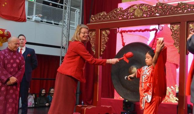 Burgemeester Pauline Krikke opent in het Atrium het Chinees Nieuwjaar door op de geluksgong te slaan.