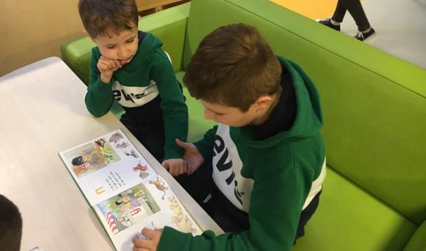 Glenn uit groep 7 leest zijn broertje Renzo uit groep 2 voor. Eigen foto