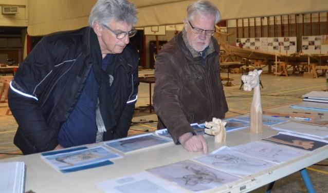 Dick Velders(l) en Coos van der Hoek vergelijken de ingezonden ontwerpen in een koude Vikinghal. FOTO: Ben Blom