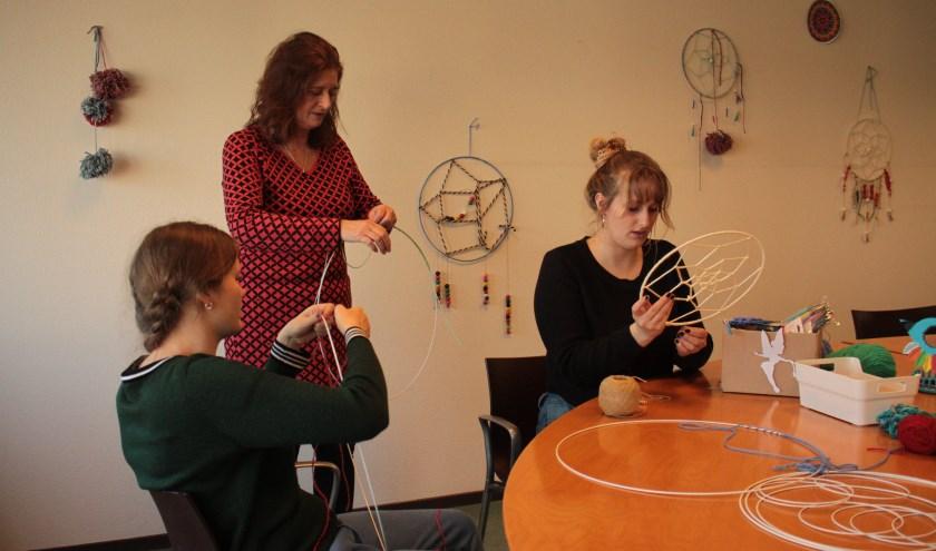 Client Nora, Marguerite en vrijwilligster Nina houden zich bij Het Andere Atelier bezig met de activiteit dromenvangers maken.