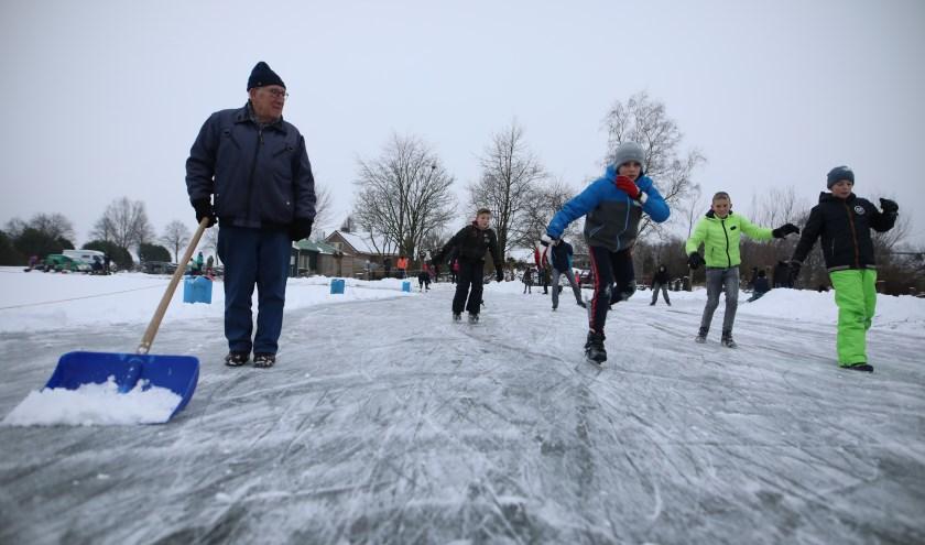 Wim Peters schuift sneeuw van de ijsbaan af. Op 24 januari ging de ijsbaan van ijsclub De Molenkolk uit Steenderen open.