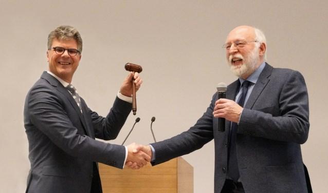 Commissaris van de Koning Hans Oosters (links) ontvangt de voorzittershamer uit de handen van vicevoorzitter Kees de Kruijf.