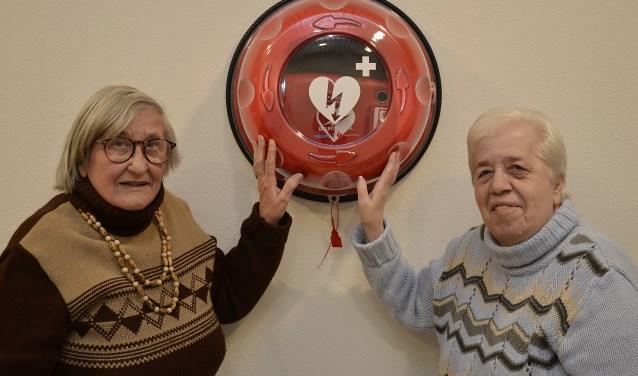 Mevrouw Vlastuin en mevrouw Bouman, bewoners van De Pelgromhof in Zevenaar, bewonderen de nieuwe AED die beschikbaar is voor de hele molenwijk. (foto: Ab Hendriks)