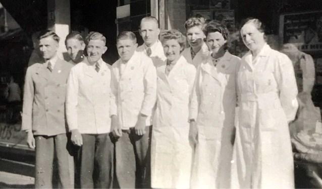 De vader van Jan Meijerink (links) met het personeel en zijn moeder (rechts) voor de winkel vóór het bombardement.
