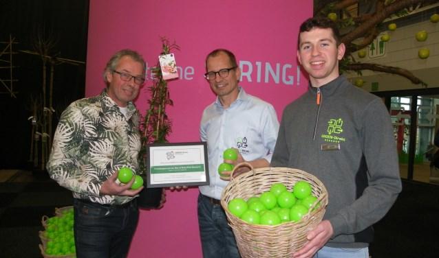 Luuk van der Werf (re) is 'ballenjongen' tijdens de Voorjaarsbeurs. De plant met de meeste ballen komt van Albrecht Brands (li). Hij krijgt de prijs van Hans Kok van GROEN-direkt. FOTO: Morvenna Goudkade.