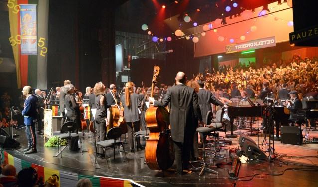 Het thema 'draoit 'm 'ns om' wordt hier mooi uitgebeeld. Het orkest staat omgekeerd naar de Plebstribune terwijl spreekstalmeester Jan Roosen de bezoekers in de grote zaal aankijkt.