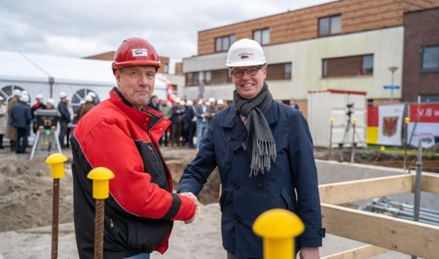 wethouder Willems en uitvoerder Nijhuis feliciteren elkaar met start bouw