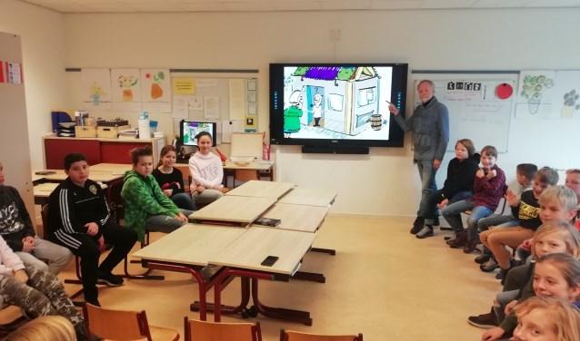 Energie-Ambassadeur Jaap Holwerda heeft zijn oude beroep als leraar weer even opgepakt en vertelt de kinderen van De Kring hoe ook zij goede energie-ambassadeurs kunnen worden.FOTO: Marcel Bos