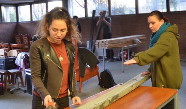 Sevda Meral werkt onder begeleiding van Dymphna van der Meer aan een van de bankjes voor het Speelpark Horden. Achter hen jongerenwerker Eno Middelham met het hout voor de basisschool.