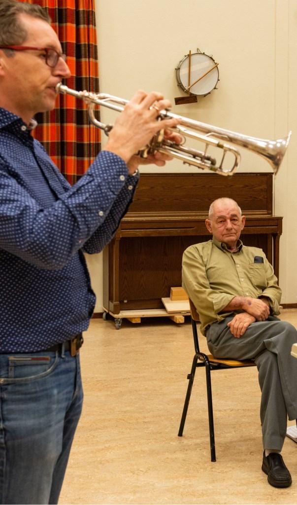 Evert Stokkink luistert geëmotioneerd hij naar dirigent/trompettist Rudolf Weges.  Foto: Dennis Dekker © Persgroep