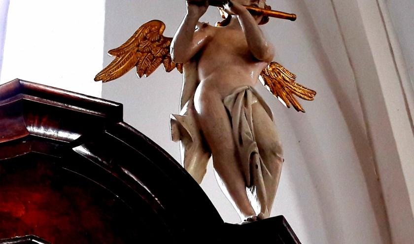 Op het kabinetorgel staan drie muzikale engelen, die toezien op de uitvoering van de strijd tussen de goede en de kwade engelen.
