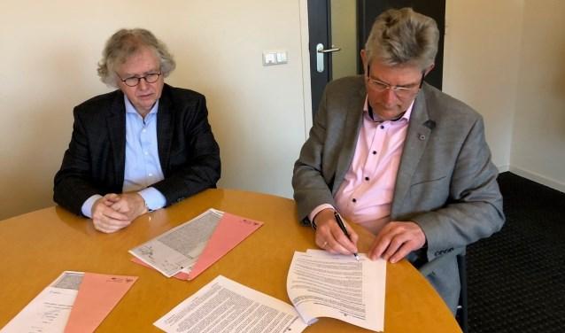 Gerrit Niezink en wethouder Johan Coes ondertekenen de overeenkomst. Foto: Gemeente Wierden.