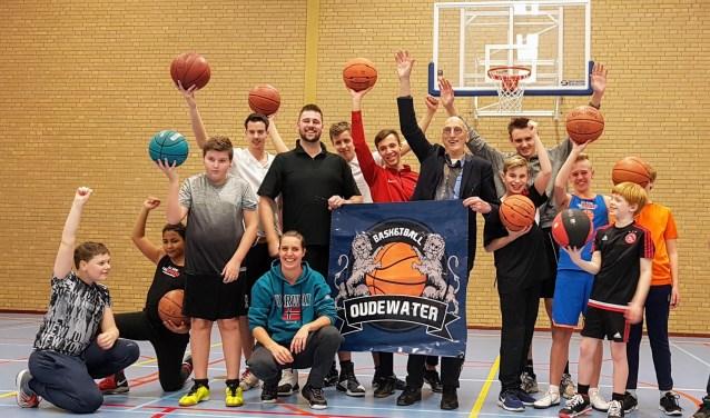 Wethouder Walther Kok te midden van de basketballers, blij met de twee aangeschafte wedstrijdbaskets voor sportzaal De Eiber. (Foto: Ellen van Leeuwen)