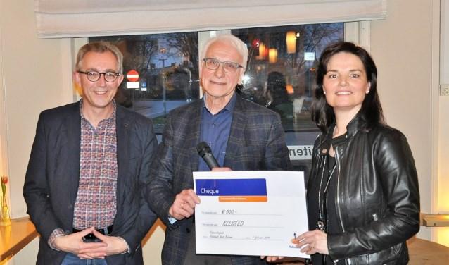 Gerrit de Weerd (midden) overhandigt een cheque aan Caroline en Harry van der Linden.