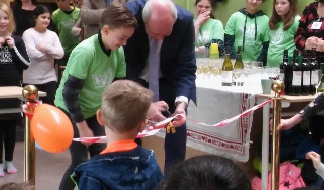 Wethouder Kees Geldof knipt het lint door ter ere van de opening van het Kindcentrum op 20 maart.