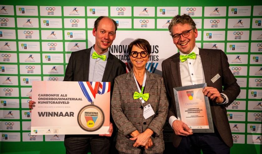 Daan Quaars (l) en Gosewin Bos (r) tonen trots hun gewonnen prijs. In het middag dagvoorzitter Chantal Verspaille. FOTO: PATRICK VAN BEEK