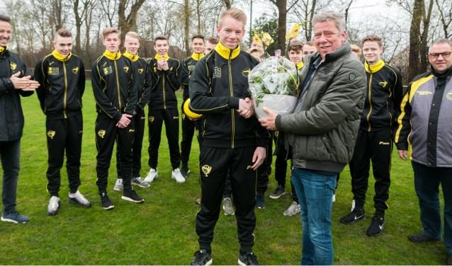 Henk van Os van Van Zon Arbeidsbemiddeling neemt een fraai bloemstuk in ontvangst van aanvoerder Jochem van 't Oever van VSCO'61 JO17-1. (Foto: VSCO'61)