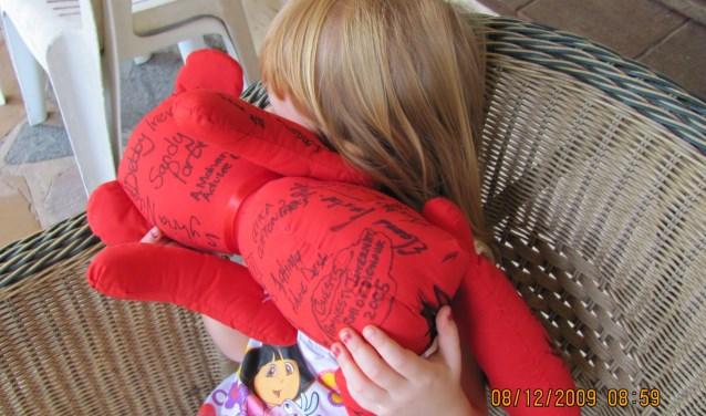 Een meisje, met de beer die haar casus beschrijft. (verjaard en vrjigegeven)