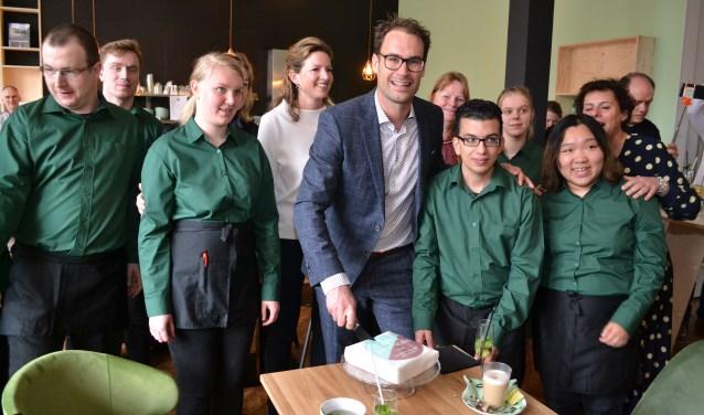 Wethouder Peter Heijkoop snijdt de eerste taart aan, geholpen door medewerkers van het leescafé. (foto: Arco van der Lee)