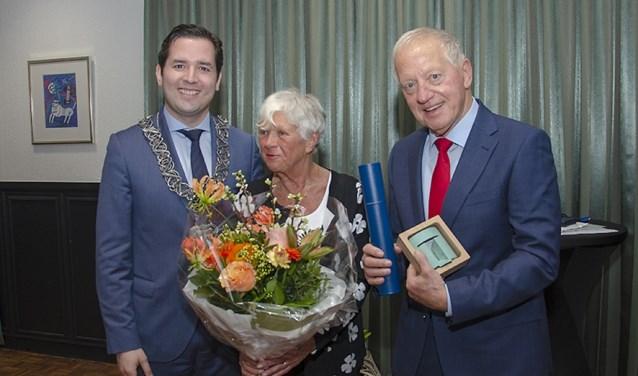 Jan Panhuijzen met de onderscheiding. Naast hem zijn vrouw en wethouder Erik de Ridder. Het uitreiken van de Tilburg Trofee is een van de laatste  optredens van de aanstaande watergraaf.