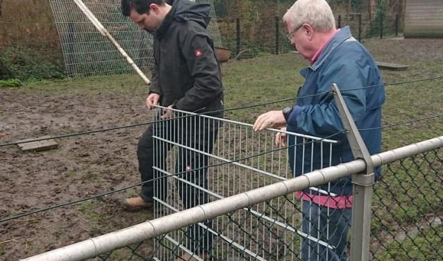 Voorzitter Stinus van Wakeren en Erik Jansen zetten hek.