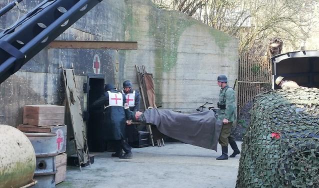 'Soldaten' van het Rode kruis rennen af en aan met gewonden naar de hospitaalbunker tijdens de filmopnames. Foto: Conny den Heijer
