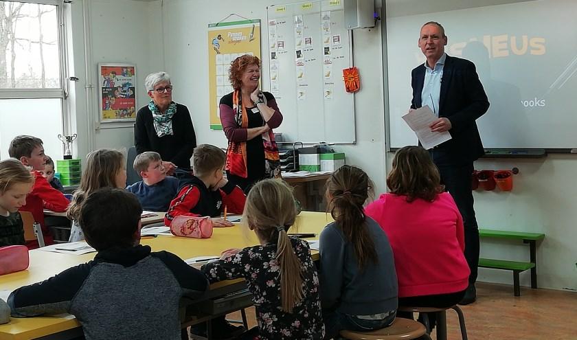 Wethouder Jos Hoenderboom leest groep 5/6 van de Ludgerusschool voor. Links naast hem educatiemedewerkster Annita Oonk van de Bibliotheek Oost-Achterhoek, die de lessen in Zwolle zal gaan verzorgen.