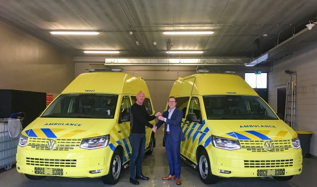 Wagenparkbeheerder Wim Treurniet (links) van de Ambulancedienst neemt de Zorgambulances officieel in ontvangst van manager bedrijfswagens Rob van der Velden van VW-dealer Ames. (Foto Frederike Slieker)